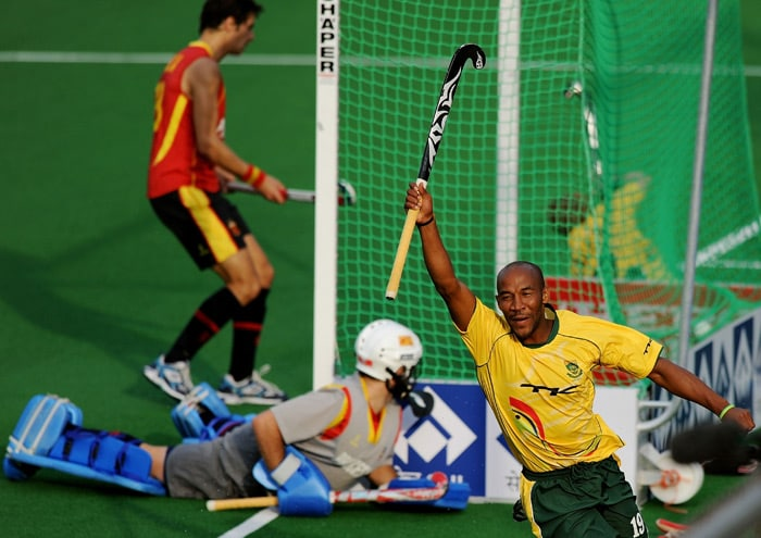 South African hockey player Julian Hykes (#19, R) raises his stick to celebrate scoring a goal against Spain during their hockey World Cup 2010 match at the Major Dhyan Chand Stadium in New Delhi. (AFP Photo)