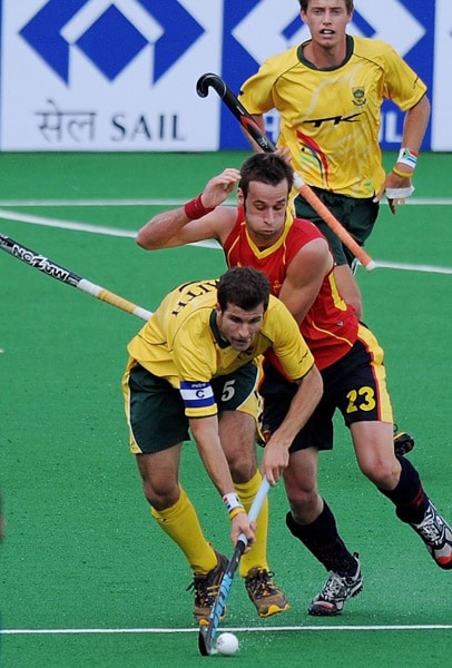 Spanish hockey player David Alegre (#23, C ) vies for the ball with South African Austin Smith (#5, L) during their hockey World Cup 2010 match at the Major Dhyan Chand Stadium in New Delhi. (AFP Photo)