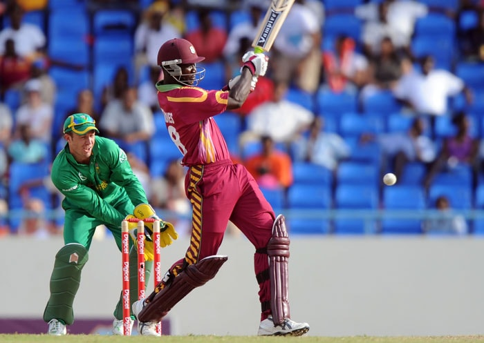 South African wicketkeeper AB de Villiers looks on as West Indies batsman Darren Sammy hits the ball. West Indies won the toss and chose to bowl. (AFP PHOTO)