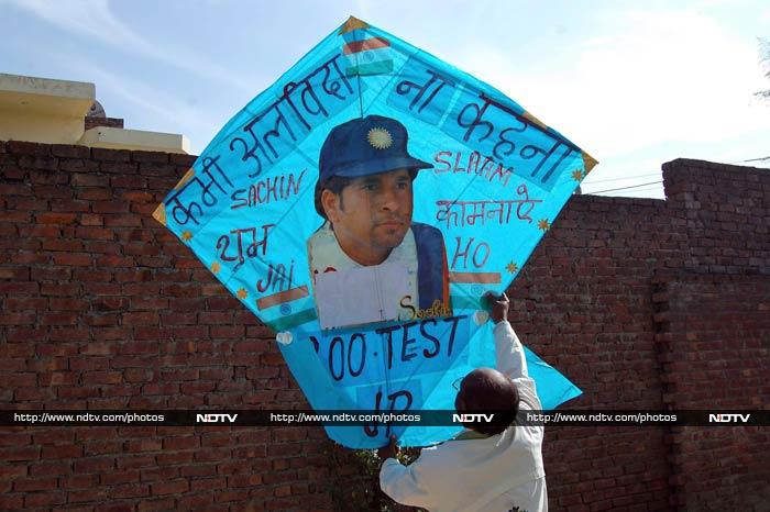 """Kitemaker Jagmohan Kanojia holds up a kite with a portrait of Tendulkar and a message that reads: """"Never say farewell"""" in Amritsar."""