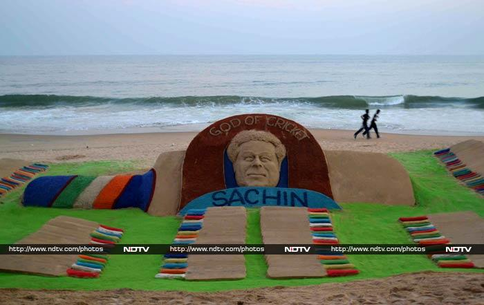 Joggers pass a sand sculpture of two hundred cricket bats, created by sand artist Sudersan Pattnaik on Golden Sea Beach at Puri.