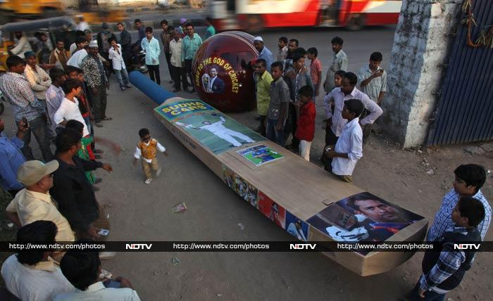 Fans look at vehicles designed in the shape of a bat and ball with posters of Sachin, displayed in Hyderabad.