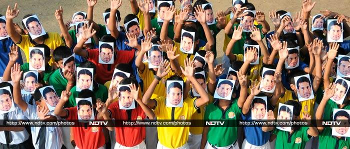 Indian school students wear masks of Sachin Tendulkar at an event to honor him in Nagpur.
