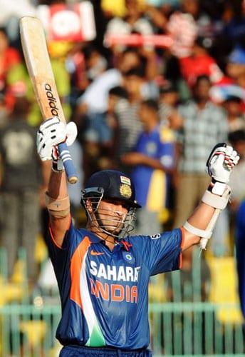 Sachin Tendulkar raises his bat in the air to celebrate his century during the Compaq Cup tri-series final match against Sri Lanka in Colombo. (AFP Photo)