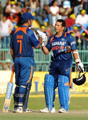 Sachin Tendulkar is congratulated by his Indian captain Mahendra Singh Dhoni after scoring a century during the Compaq Cup tri-series final match against Sri Lanka in Colombo. (AFP Photo)
