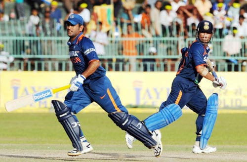 Mahendra Singh Dhoni and teammate Sachin Tendulkar run between wickets during the Compaq Cup tri-series final match against Sri Lanka in Colombo. (AFP Photo)