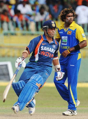 Sachin Tendulkar runs between wickets as Sri Lankan cricketer Lasith Malinga looks on during the Compaq Cup tri-series final match against Sri Lanka in Colombo. (AFP Photo)