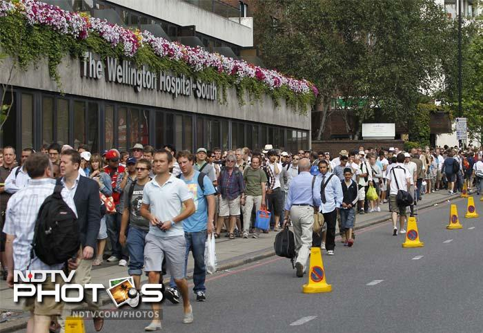 Cricket fans queue down Wellington Road to buy tickets for the last day of the first Test between England and India at Lord's Cricket Ground. (AFP Photo)