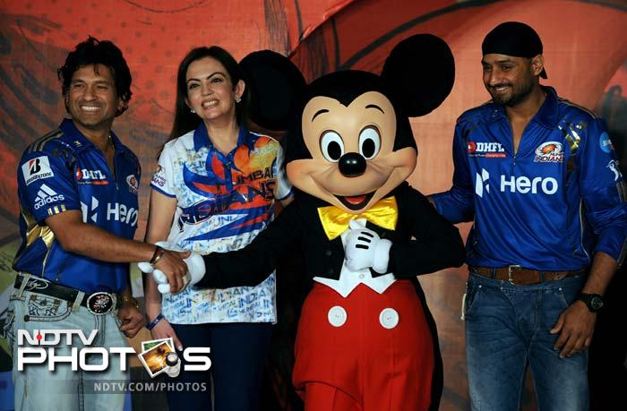 Sachin Tendulkar (L) shakes hands with the Disney character Mickey Mouse (2R) as team captain Harbhajan Singh (R) and team owner Nita Ambani (2L) look on. (AFP PHOTO/Indranil MUKHERJEE)