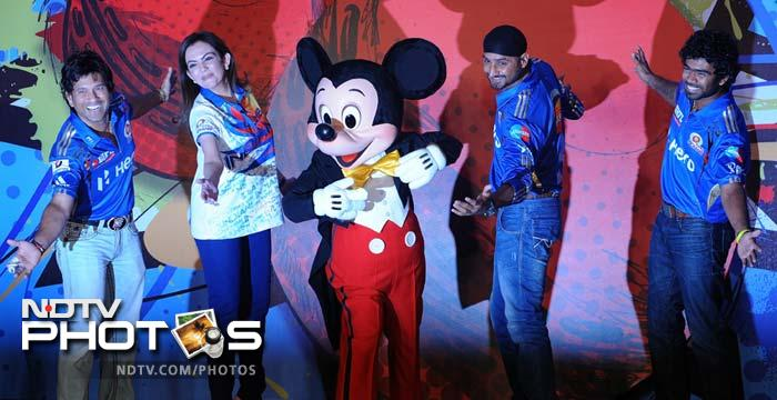 Mumbai Indians' bowler Lasith Malinga (R) joins in the fun and poses with team-mate Sachin Tendulkar (L), team owner Nita Ambani (2L) and team captain Harbhajan Singh (2R) with Disney character Mickey Mouse (C). (AFP PHOTO/Indranil MUKHERJEE)