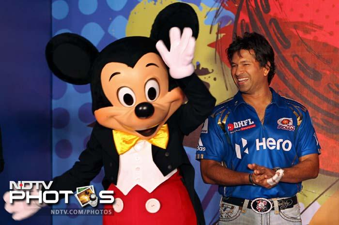 Sachin Tendulkar poses for a photograph with Mickey Mouse during the unveiling of Mumbai Indians' limited edition merchandise range called 'Mickey Cricket' in Mumbai. (AP Photo/ Rajanish Kakade)