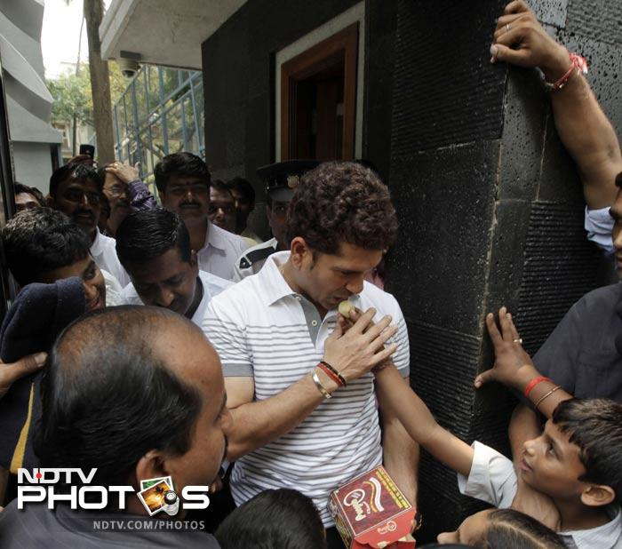 Sachin Tendulkar receives sweets from school children who arrived to greet him. (AP Photo)