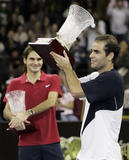Pete Sampras, right, and Roger Federer celebrate after a friendly match in Macau.