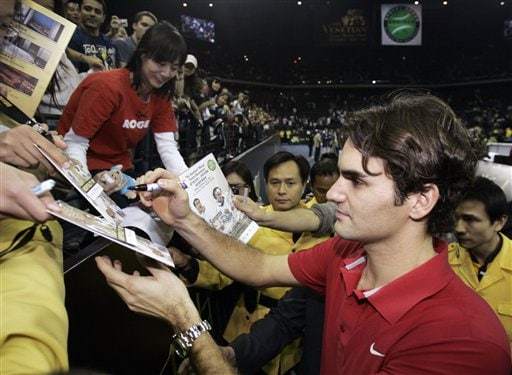 Roger Federer signs autographs to his fans.