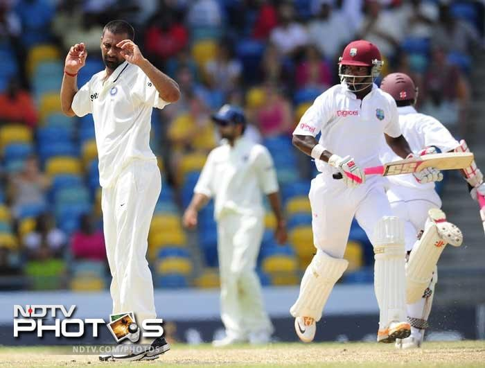 Praveen Kumar reacts as West Indies batsmen Darren Bravo (C) and Shivnarine Chanderpaul score during the fifth day of the Test match. (AFP Photo)