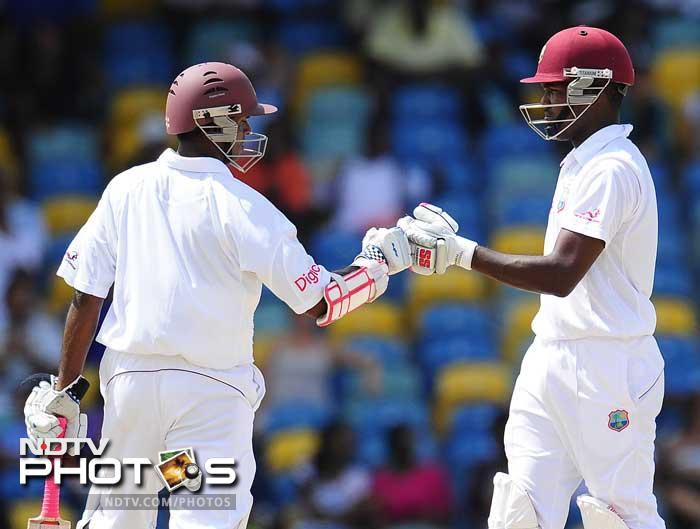 West Indies batsmen Darren Bravo (R) and Shivnarine Chanderpaul celebrate a boundary during the fifth day of the Test match. The duo ensured the team's safety with their 54-run partnership. (AFP Photo)