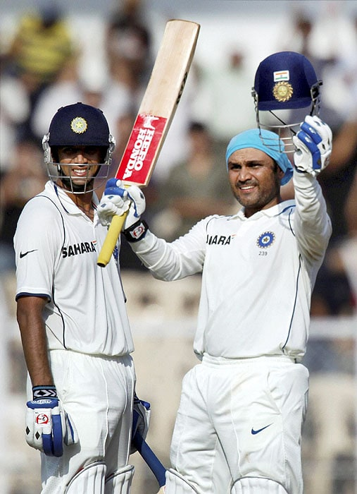 India's Virender Sehwag ackowledges the crowd after scoring a double century, as teammate Rahul Dravid looks on during the second day of the third Test match against Sri Lanka in Mumbai. (AP Photo)