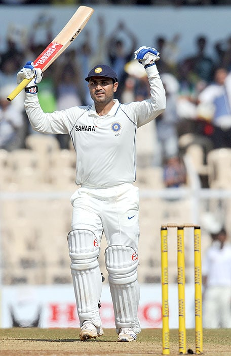 India's Virender Sehwag raises the bat after scoring a century (100 runs) during second day of the third Test against Sri Lanka in Mumbai on Thursday. (AFP Photo)