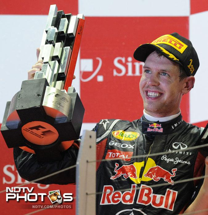 Red Bull-Renault driver Sebastian Vettel of Germany lifts the trophy on the podium after winning the Formula One Singapore Grand Prix. (AFP Photo)