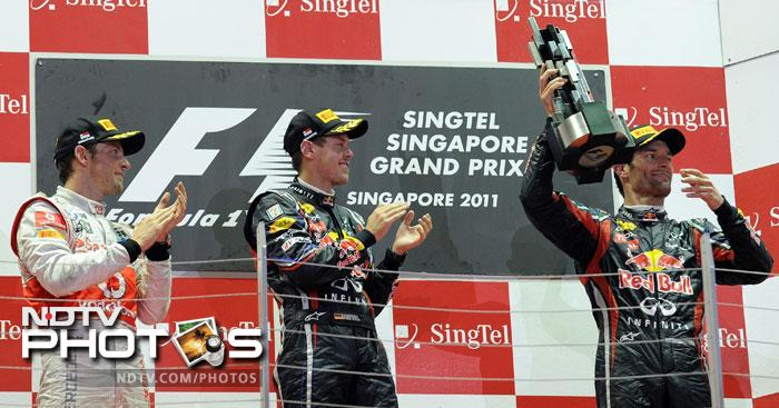 Winner Red Bull-Renault driver Sebastian Vettel of Germany (C) and second-placed McLaren-Mercedes driver Jenson Button of Britain (L) watch as third-placed Red Bull-Renault driver Mark Webber of Australia poses with his trophy on the podium during the awards ceremony for Formula One's Singapore Grand Prix. Sebastian Vettel demonstrated his supremacy when he won the Singapore Grand Prix to move within a point of becoming the youngest double world champion in Formula One history. (AFP Photo)