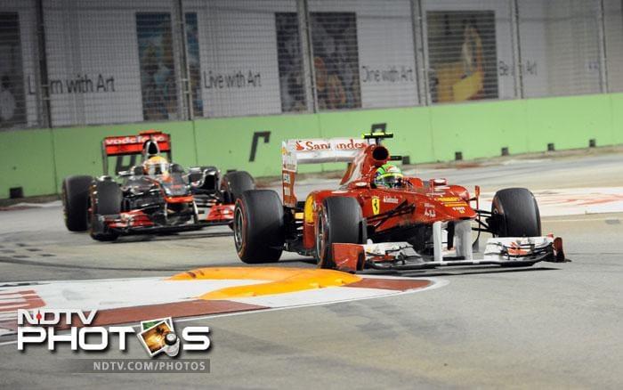 Ferrari driver Felipe Massa of Brazil and McLaren-Mercedes driver Lewis Hamilton of Britain take a bend during the Formula One Singapore Grand Prix in Singapore. (AFP Photo)