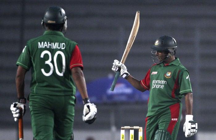 Bangladesh's Mohammad Ashraful raises his bat to celebrate scoring a half-century as teammate Mahmudullah Riyad walks to congratulate him during their first One-Day International of the tri-series against Sri Lanka in Dhaka. (AP Photo)