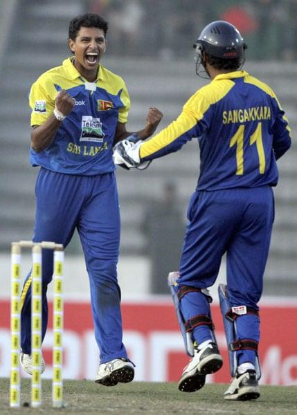 Sri Lanka's Suraj Randiv celebrates with captain Kumar Sangakkara the dismissal of Bangladesh's Mushfiqur Rahim during their first One-Day International of the tri-series in Dhaka. (AP Photo)