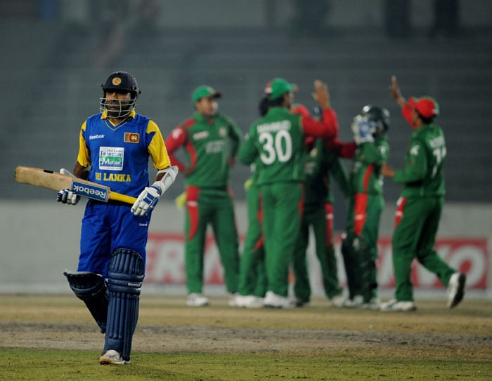 Mahela Jayawardene leaves the ground after his dismissal as Bangladeshi cricketers celebrate during the fourth ODI of the tri-series in Dhaka. (AFP Photo)