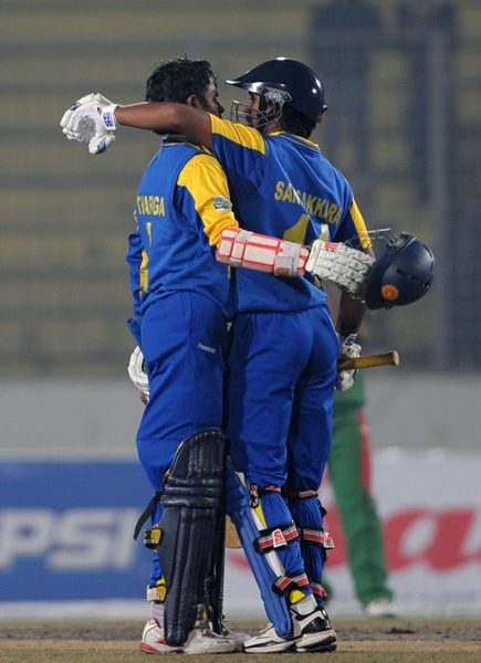 Upul Tharanga is embraced by teammate Kumar Sangakkara after scoring a century (hundred runs) during the fourth ODI of the tri-series in Dhaka. (AFP Photo)