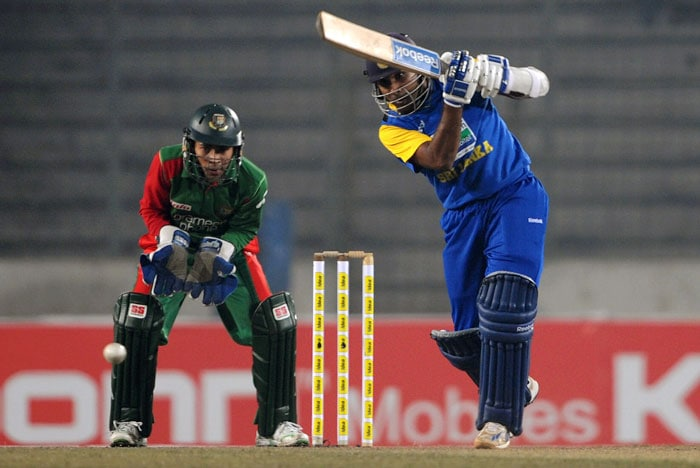 Mahela Jayawardene is watched by Mushfiqur Rahim as he plays a stroke during the fourth ODI of the tri-series in Dhaka. (AFP Photo)