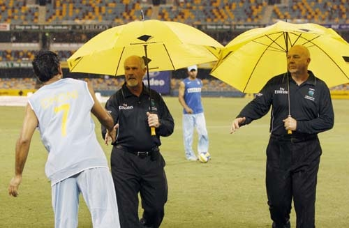Indian cricket captain MS Dhoni, left, shakes the hands of umpires Rudi Koertzen and Steve Davis, right, after their One-Day cricket international against Sri Lanka was abandoned due to rain in Brisbane on Tuesday, February 5, 2008.