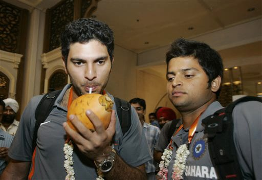 Yuvraj Singh drinks coconut water as team-mate Suresh Raina looks on upon their arrival at a hotel in Colombo on Monday. (AP Photo)