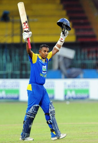 Sri Lanka's Thilan Samaraweera raises his bat and helmet in celebration after scoring a century (100 runs) during the first ODI of the Tri-Nation Championship trophy in Colombo. (AFP Photo)