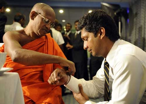 Kumar Sangakkara is blessed by a Buddhist monk in Colombo before leaving for England to play in the ICC Twenty20 World Cup. (AFP Photo)