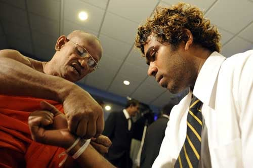 Lasith Malinga is blessed by a Buddhist monk in Colombo before leaving for England to play in the ICC Twenty20 World Cup. (AFP Photo)