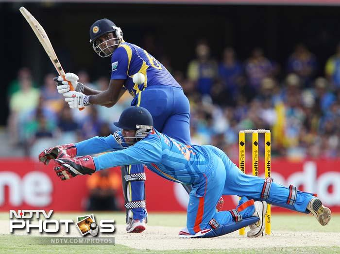 Sri Lanka's Angelo Mathews plays a shot past India's wicketkeeper Parthiv Patel, foreground, during their One Day International cricket match in Brisbane.