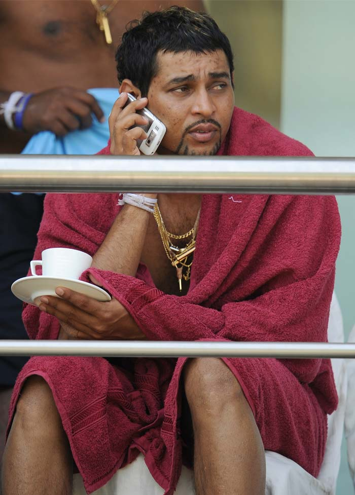 He has scored runs at the rate of bullets fired from a machine gun, in this tournament. A slightly nervous look as he talks on the phone however seems to escape Tillakaratne Dilshan even as he brandishes his chain-clad chest at the player's gallery of the stadium. (AFP PHOTO)