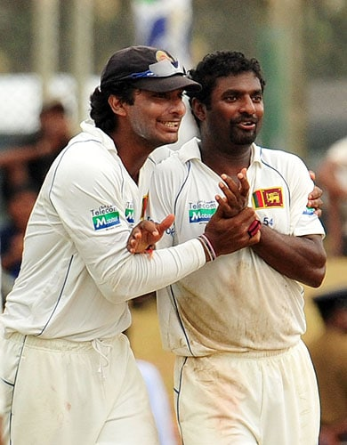 Sri Lankan cricketer Muttiah Muralitharan is congratulated by captain Kumar Sangakkara after dismissing unseen New Zealand batsman Tim McIntosh during the third day of the first Test match at The Galle International Cricket Stadium in Galle on Thursday. (AFP Photo)
