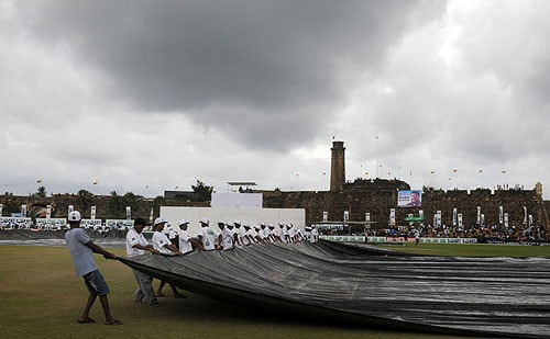 Sri Lankan groundstaff run to cover the playing surface during a spell of rain on the fourth day of the first Test match between Sri Lanka and New Zealand at The Galle International Cricket Stadium in Galle on August 21, 2009. Sri Lanka declared their second innings at 259 runs for the loss of four wickets a lead of 412 runs. (AFP Photo)