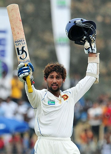 Sri Lanka's Tillekeratne Dilshan raises his bat and helmet in celebration after scoring a century during the fourth day of the first Test match against New Zealand at The Galle International Cricket Stadium in Galle on Friday. (AFP Photo)