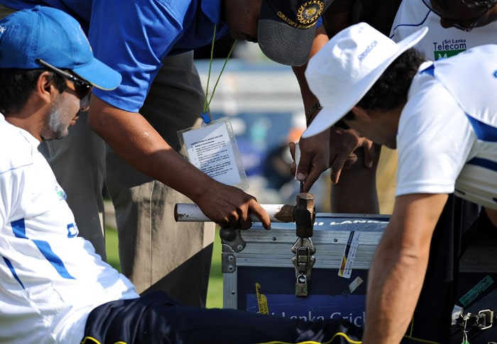 Kumar Sangakkara looks on as team officials attempt to break a lock of his equipment case after misplacing a key during a training session ahead of the third and final Test against India in Mumbai. (AFP Photo)