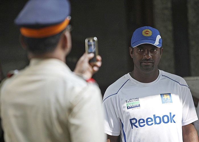 An Indian police officer takes photos of Muttiah Muralitharan during a practice session ahead of the third Test between India and Sri Lanka in Mumbai. (AP Photo)