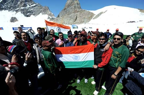 Indian former cricketers along with Indian tourists sing the national anthem before the start of a cricket match on snow in Bernese Alps in Switzerland on August 15, 2009. Indian sports tourism company Beyond Boundaries organised for the first time a cricket on Snow match. This on the Indian Independance day where a 6-a-side five over match was held at 11,333ft at Jungfrau in the Bernese Alps in Switzerland. Kapil Dev led the Indian team that won by four runs against the All Stars team led by former West Indian cricketer Allvin Kallicharran. (AFP Photo)