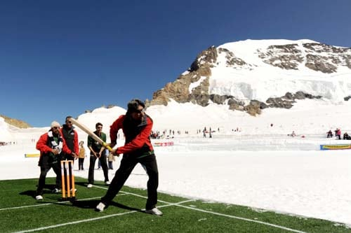 Former Indian cricketer and captain Kapil Dev plays a shot during a cricket match on snow in Bernese Alps in Switzerland. (AFP Photo)