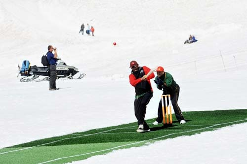 Indian Former cricketer Sandeep Patil plays a shot as West - Indian former cricketer Allvin Kallicharran keeps the wicket during a cricket match on snow in Bernese Alps in Switzerland. (AFP Photo)