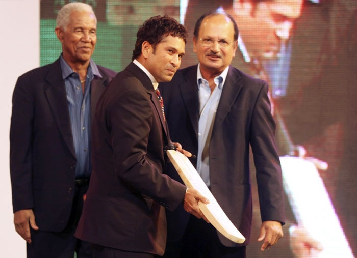 Sachin Tendulkar, centre, holds an autographed bat presented to him, as former West Indies cricketer Gary Sobers, left, and former Indian cricketer Ajit Wadekar watch, during an event in Mumbai. Tendulkar recently scored the first ever double century in One-Day International cricket. (AP Photo)