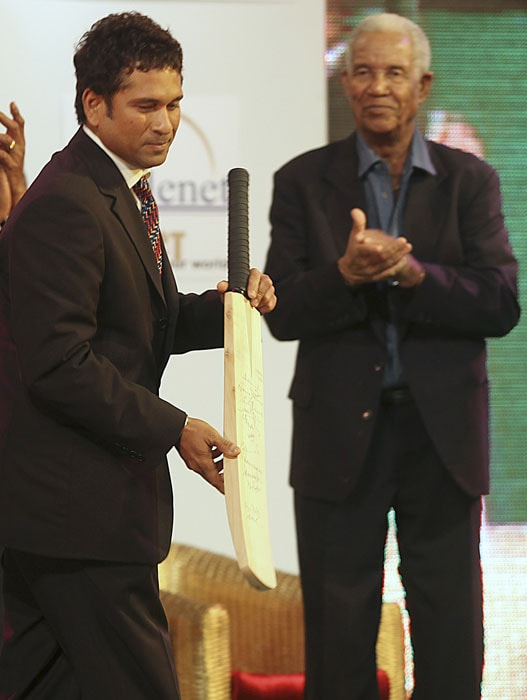 Indian cricketer Sachin Tendulkar, left, holds an autographed bat presented to him, as former West Indies cricketer Gary Sobers applauds, during an event in Mumbai. (AP Photo)