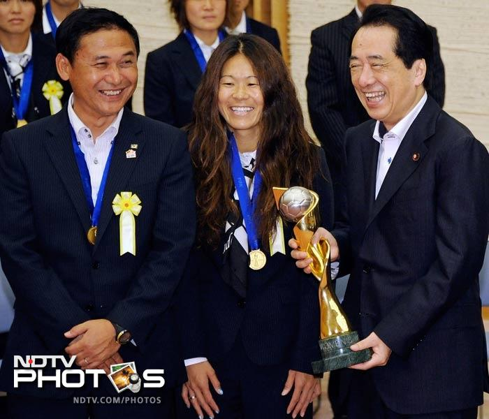 Naoto Kan smiles here as he holds the World Cup trophy that the women won on Sunday.