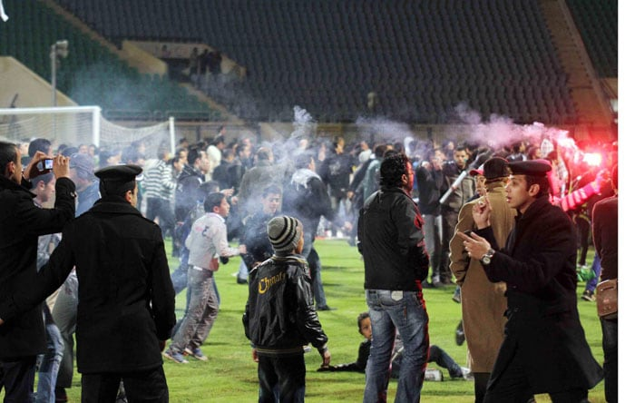 TV footage showed Al-Ahly players rushing for their locker room as fistfights broke out among the hundreds of fans swarming on to the field. Some men had to rescue a manager from the losing team as he was being beaten. Black-clothed police officers stood by, appearing overwhelmed. (AP Photo)