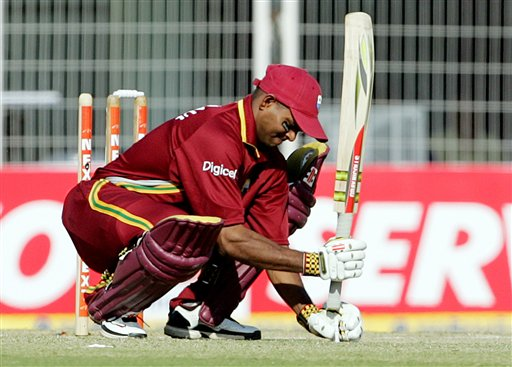 West Indies Shiv Narain Chanderpaul puts a mark on the crease with a bail and a bat while batting against India during the first one day international cricket match in Nagpur